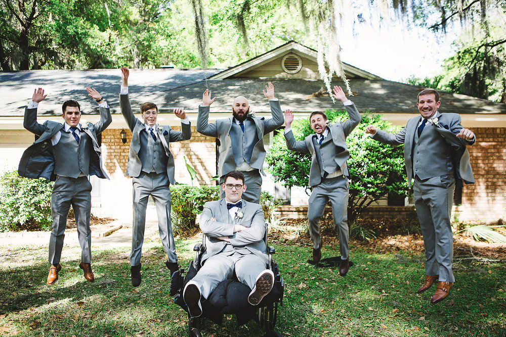 Izzy Hudgins Wedding Photography groomsmen jumping while groom sits in wheelchair with arms crossed