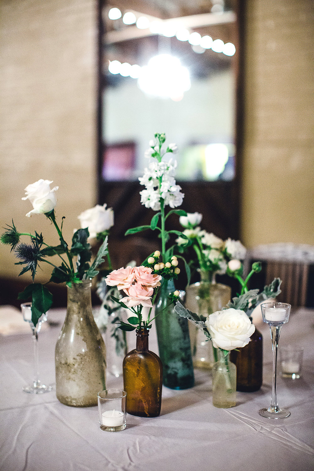 Izzy Hudgins Wedding Photography flowers in mismatched jars table centerpieces