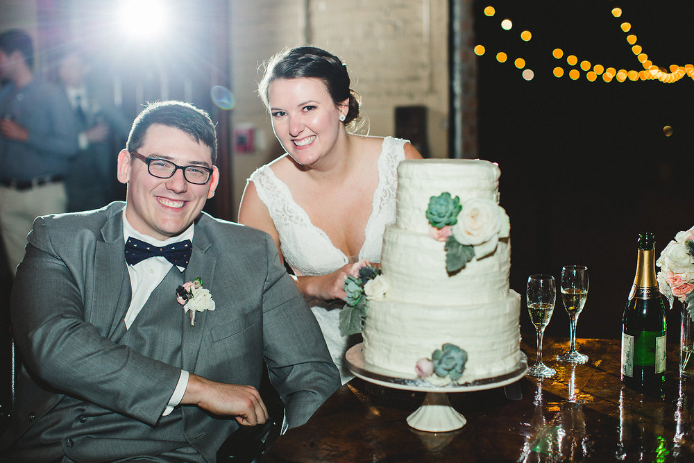 Izzy Hudgins Wedding Photography bride and groom with wedding cake