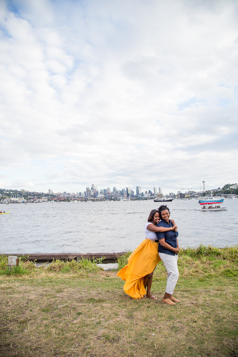 Taymah and Brittany hugging in the Gas Works Park against the Seattle skyline