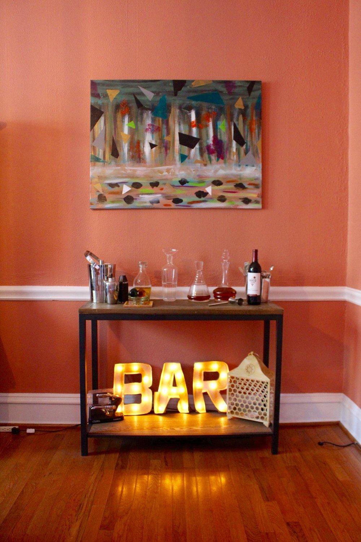 Freebird Imagery bar lights on bottom shelf of decorative hall table