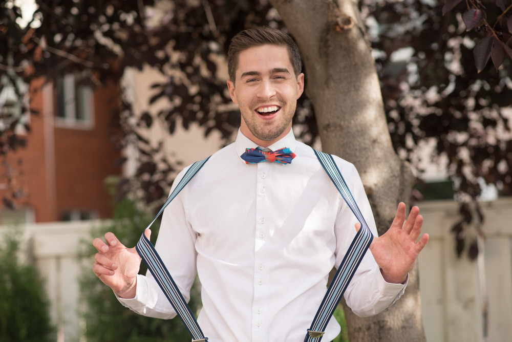 Buffy Goodman Wedding Photography groom stretching suspenders