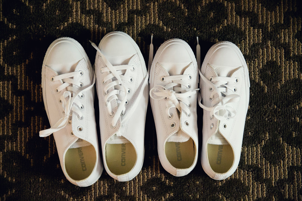 Two pairs of white Converse shoes side by side
