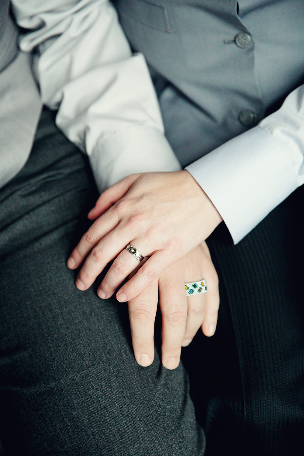 Overlapping hands with engagement rings