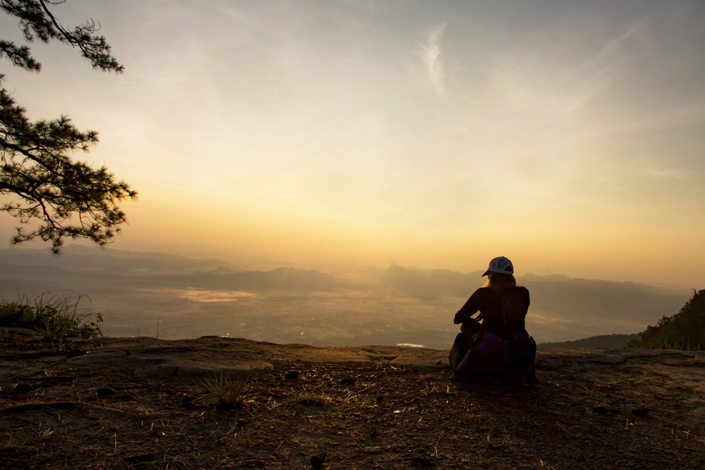 Person sitting on mountain looking out over valley and contemplating