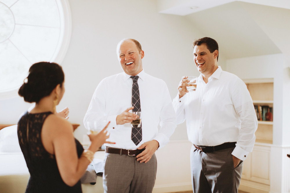 Grooms getting ready together and sipping bourbon