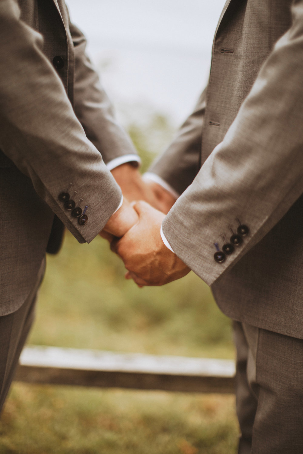 Grooms holding hands during wedding ceremony