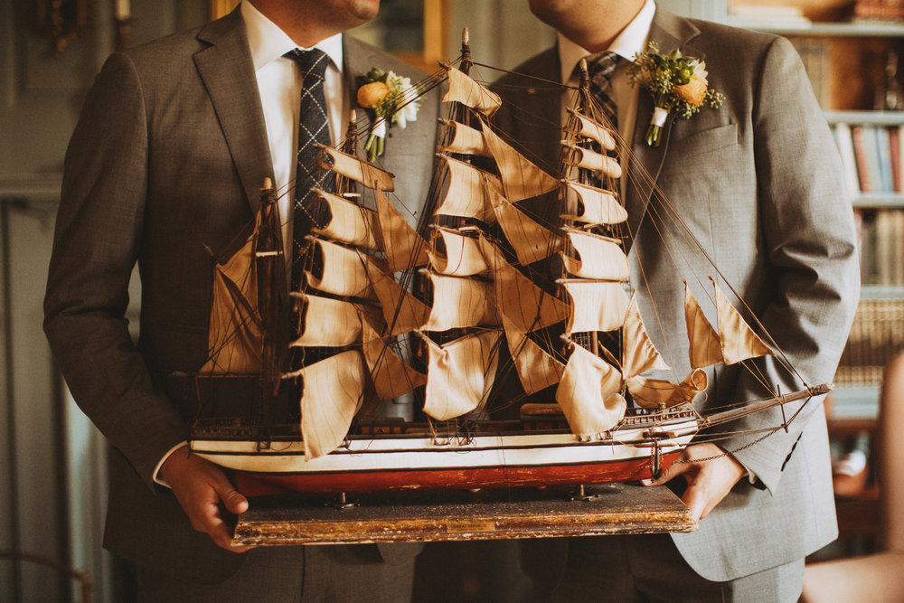 Two grooms holding a ship model