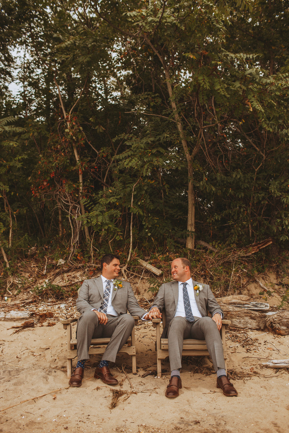 grooms sitting in wooden chairs by the water