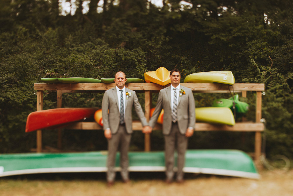 Canoes in the backdrop of a wedding portrait of two grooms