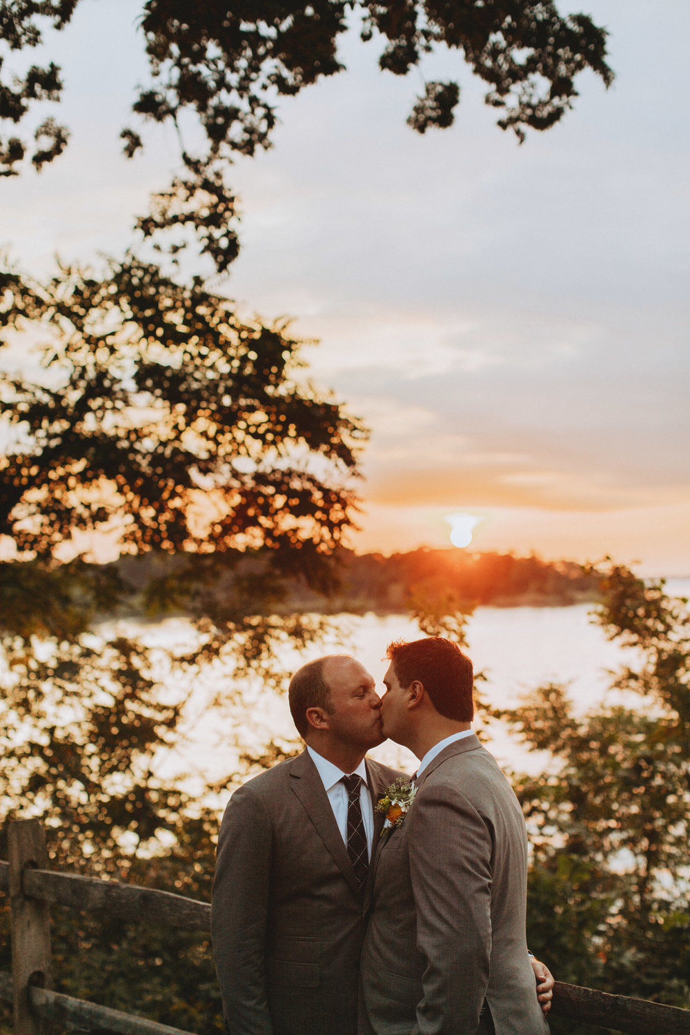two grooms kissing at sunset
