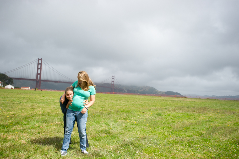 Same-sex maternity photos in San Francisco with the Golden Gate Bridge in the background.