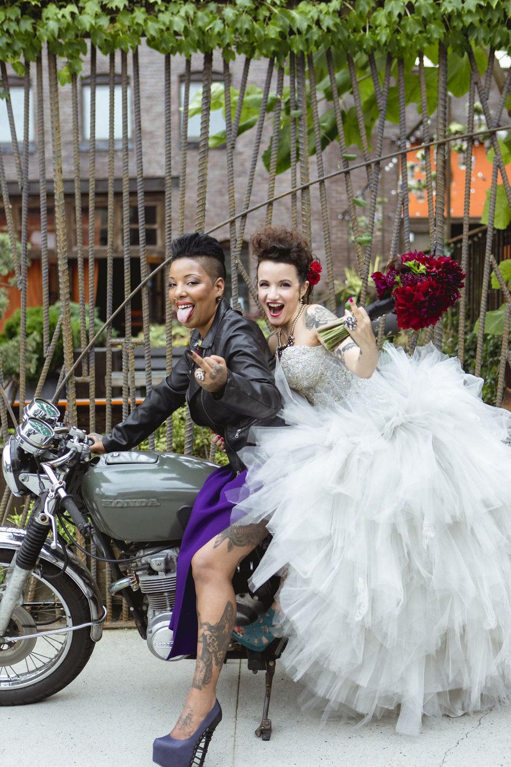 two brides flipping the bird on a motorcycle.