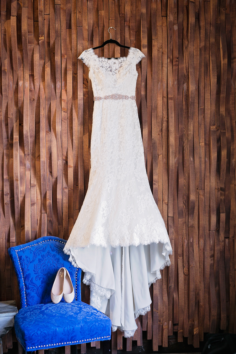 wedding gown hanging next to sparkly bridal flats