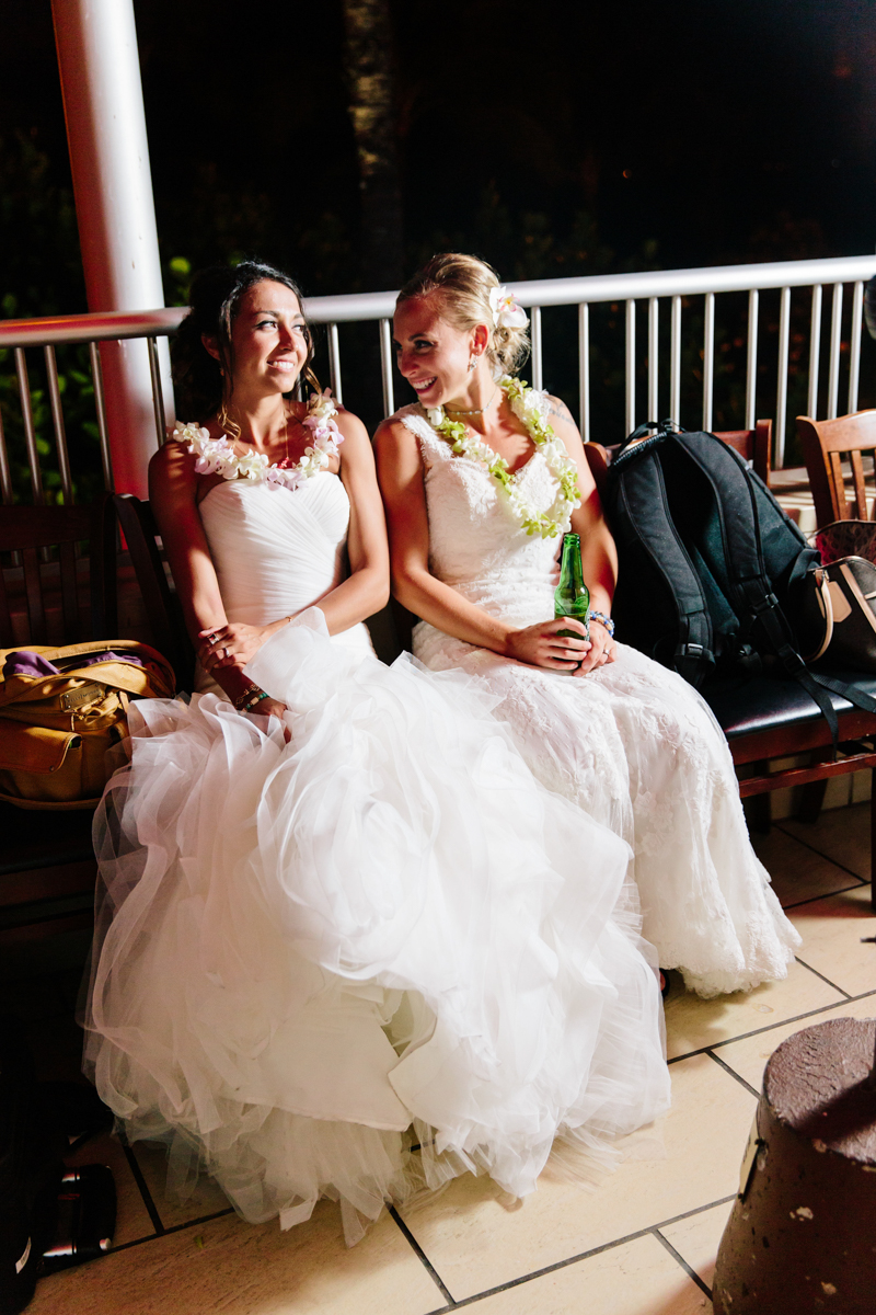 two brides laughing at their wedding reception