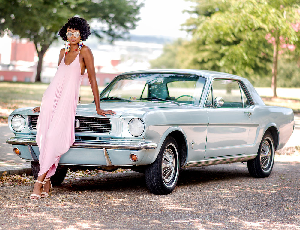 hip black woman with natural hair leaning on vintage vehicle