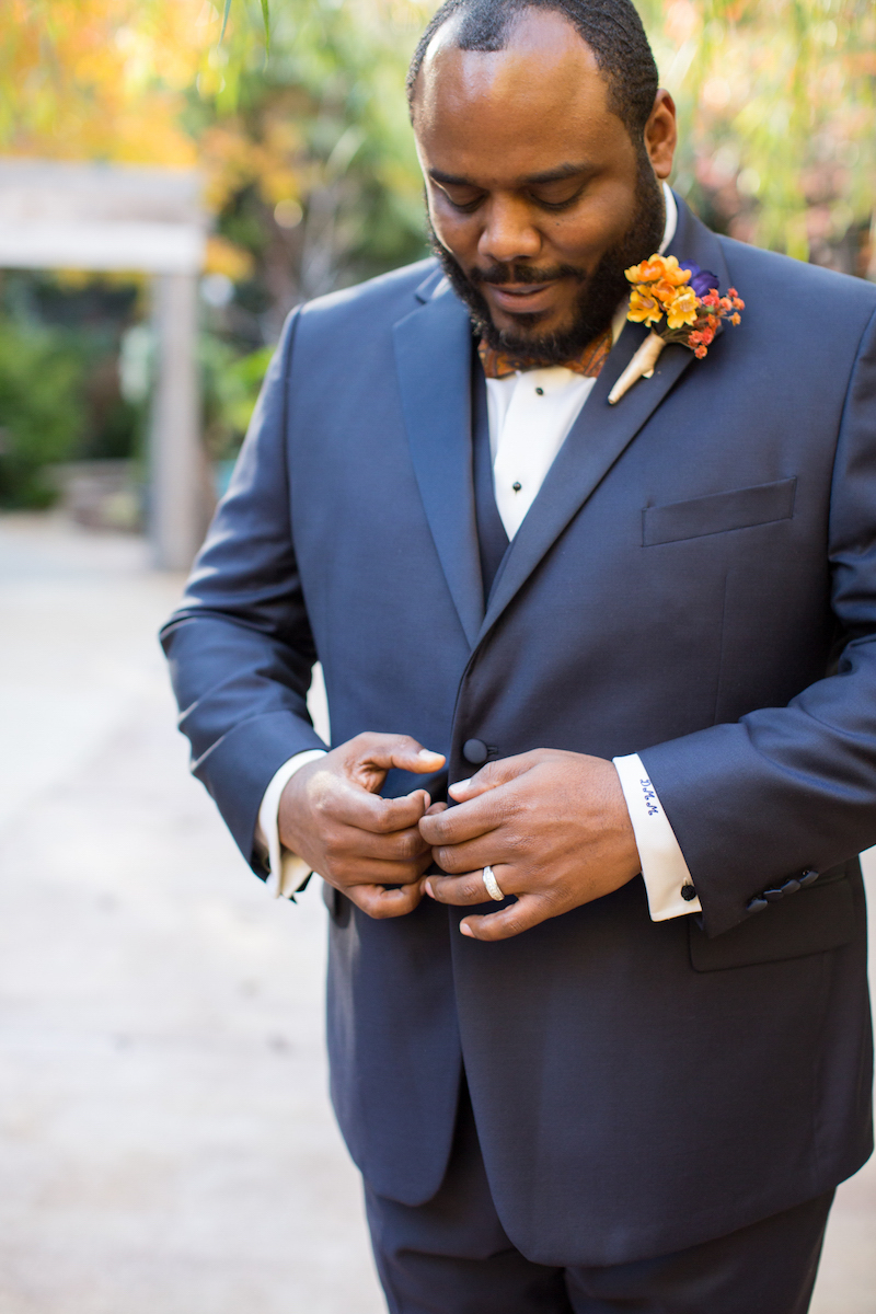 Black groom buttoning his suit