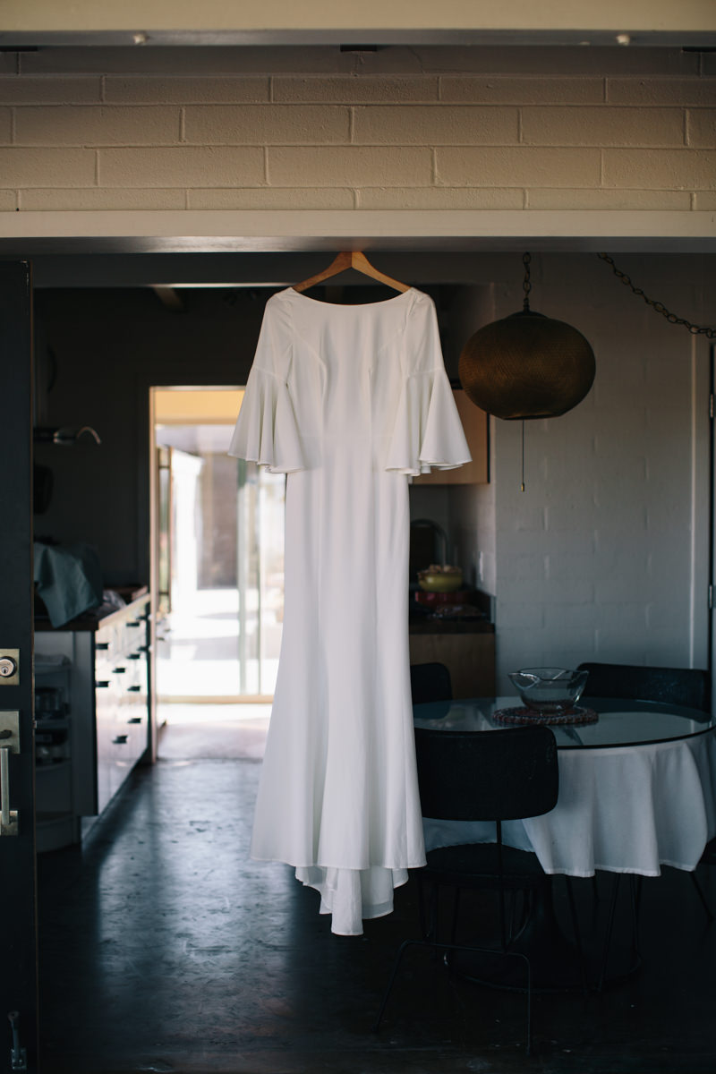 the bride's white dress hanging in the airbnb