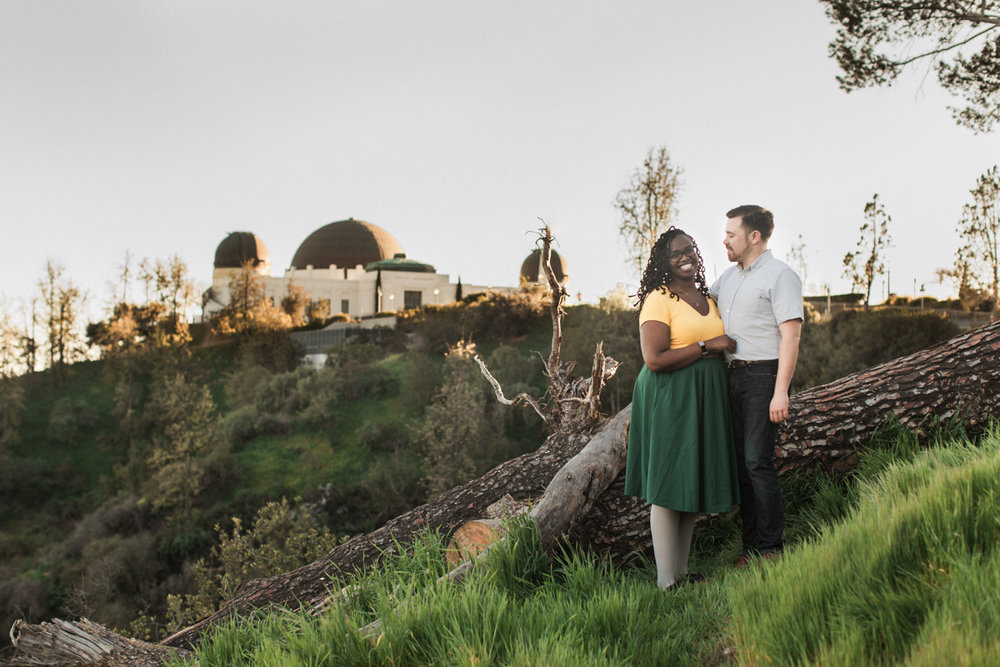 couple posed with the Griffith Observatory in the background