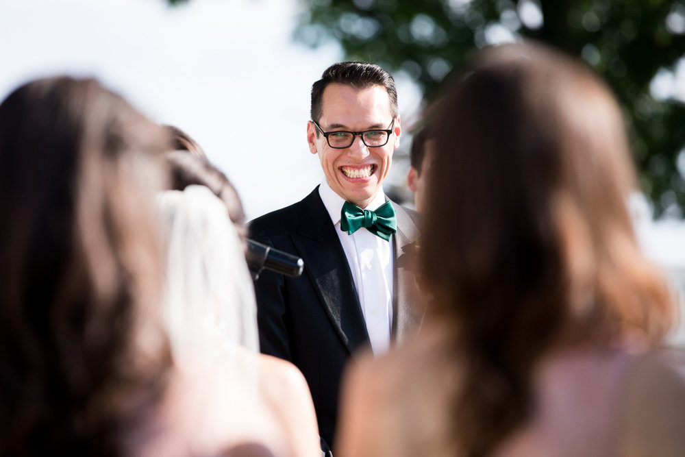 groom grinning during wedding ceremony
