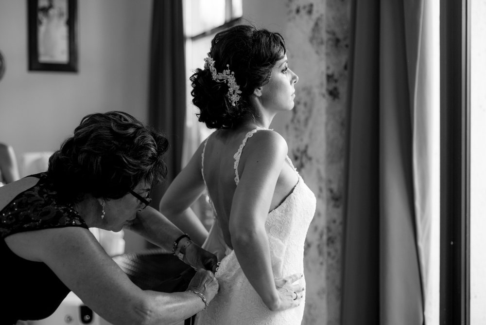 bride getting buttoned into gown