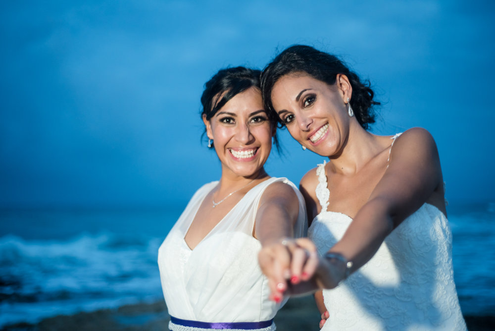 Brides at the beach at dusk at their wedding