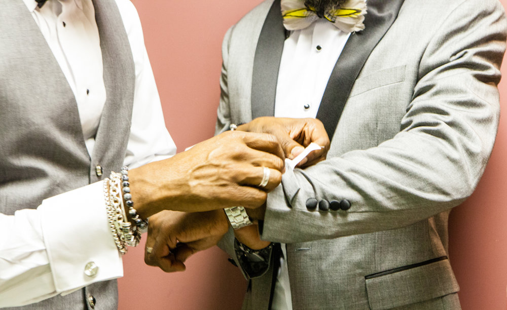 grooms helping each other getting ready