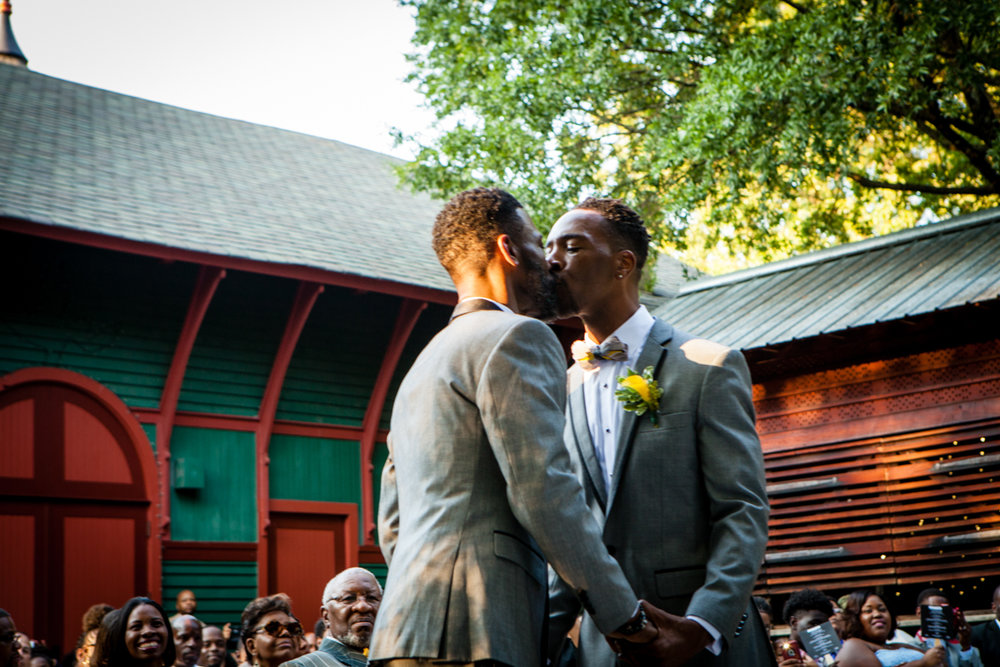 Grooms kissing at their wedding ceremony
