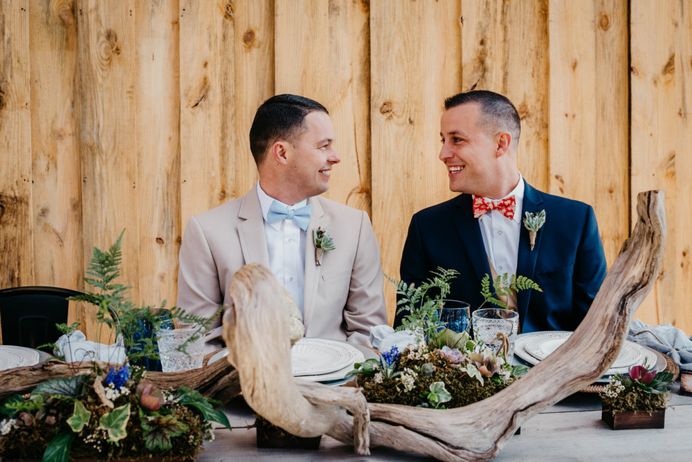 Grooms smiling at a rustic table
