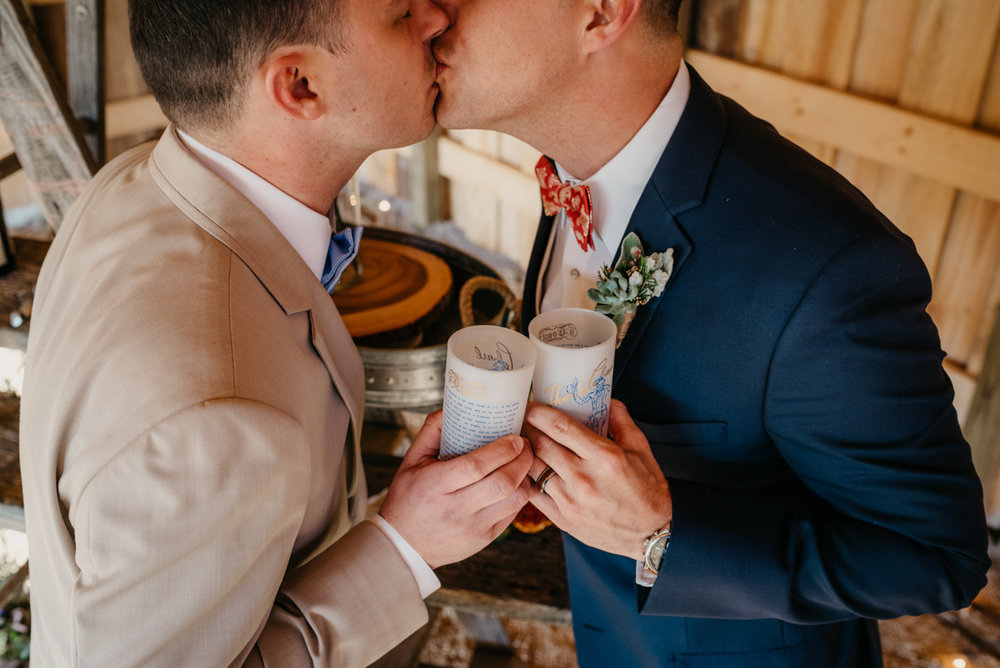 grooms toasting each other with vintage glasses