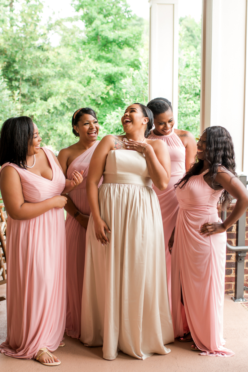 Bride and bridesmaids in blush laughing on the porch