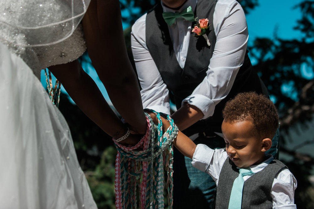 mountain elopement tying hands with son