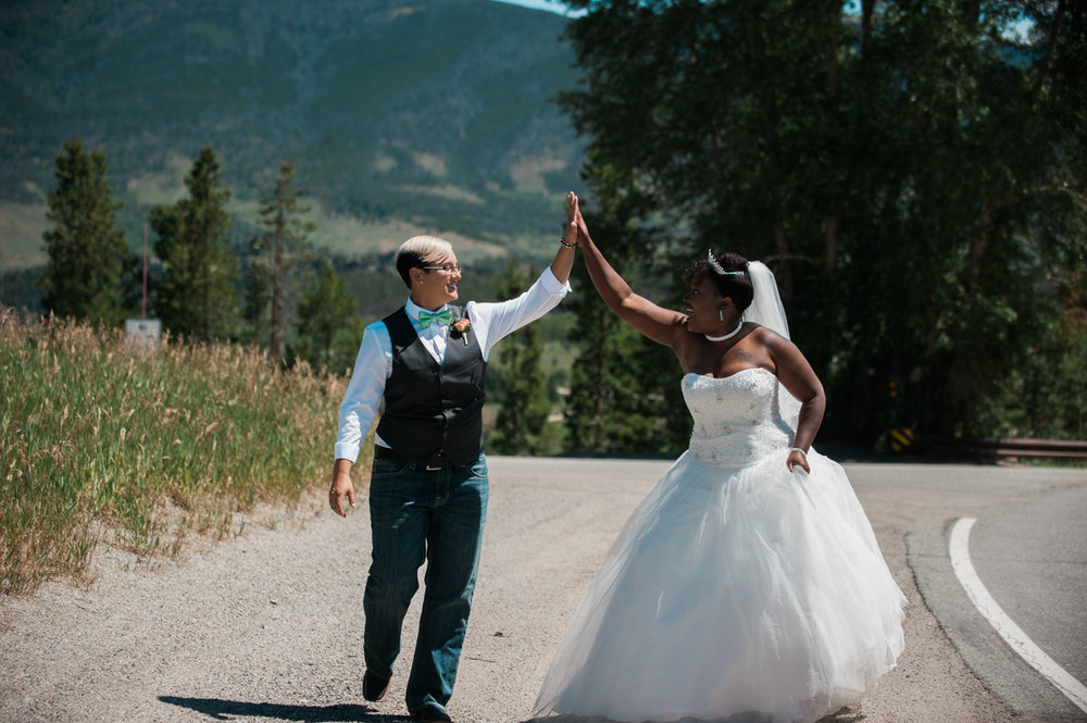 mountain elopement hands together in the air