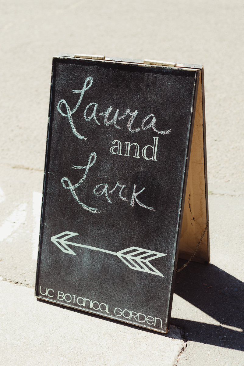 "uc berkeley garden wedding chalkboard sign reading ""laura and lark"" with an arrow beneath"