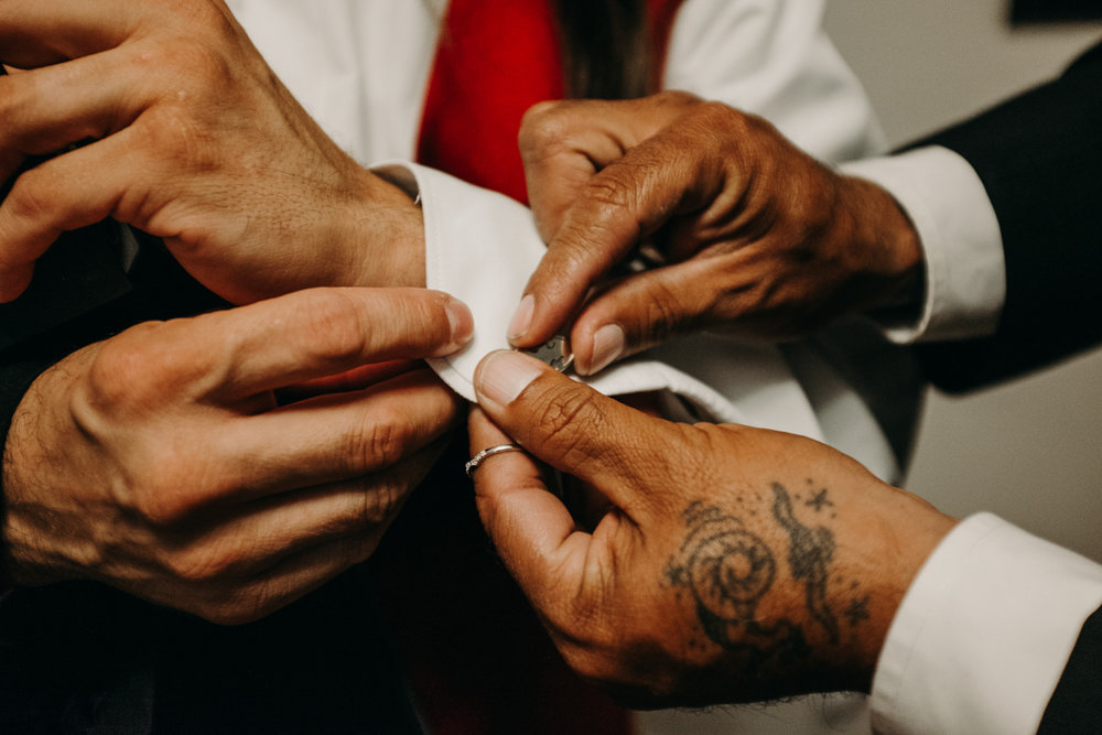 San antonio garden wedding putting on cufflinks