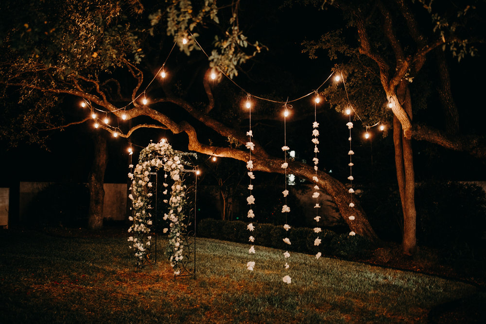 San antonio garden wedding flower arch and string lights on trees at night