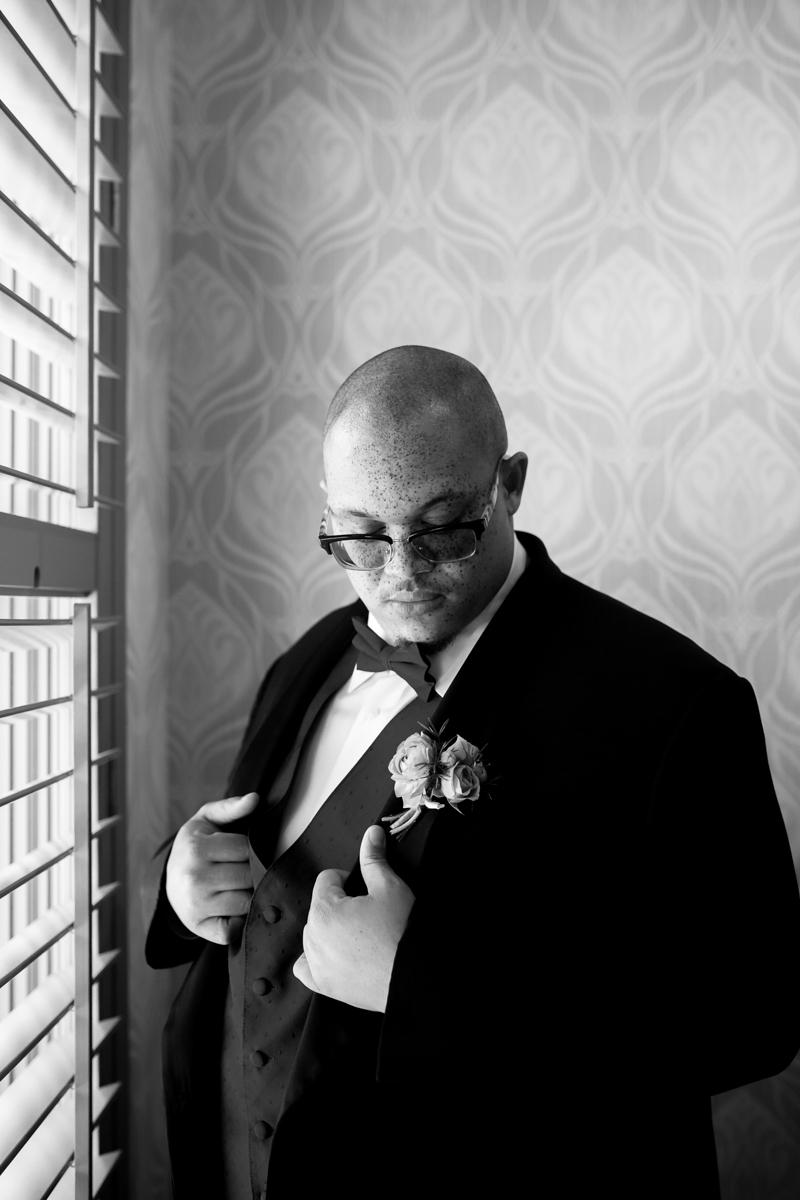 Ballroom wedding charlotte nc groom posing at window