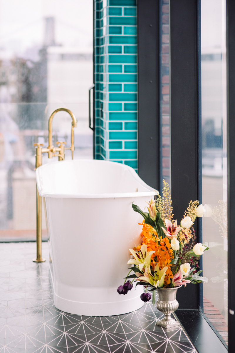 williamsburg hotel wedding shoot bathtub with floral arrangement by windows