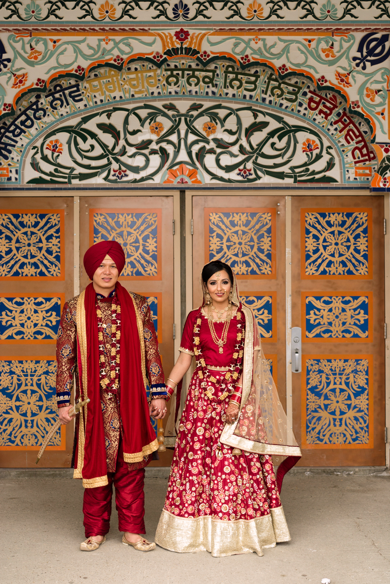 edmonton Indian and filipino wedding couple holding hands outside doors