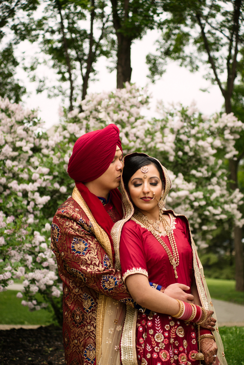 edmonton Indian and filipino wedding embrace by blooming trees