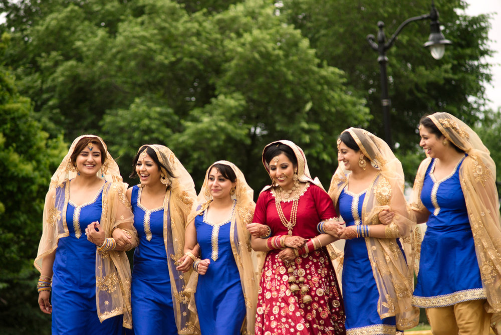 edmonton Indian and filipino wedding bride and bridesmaids walking with arms linked