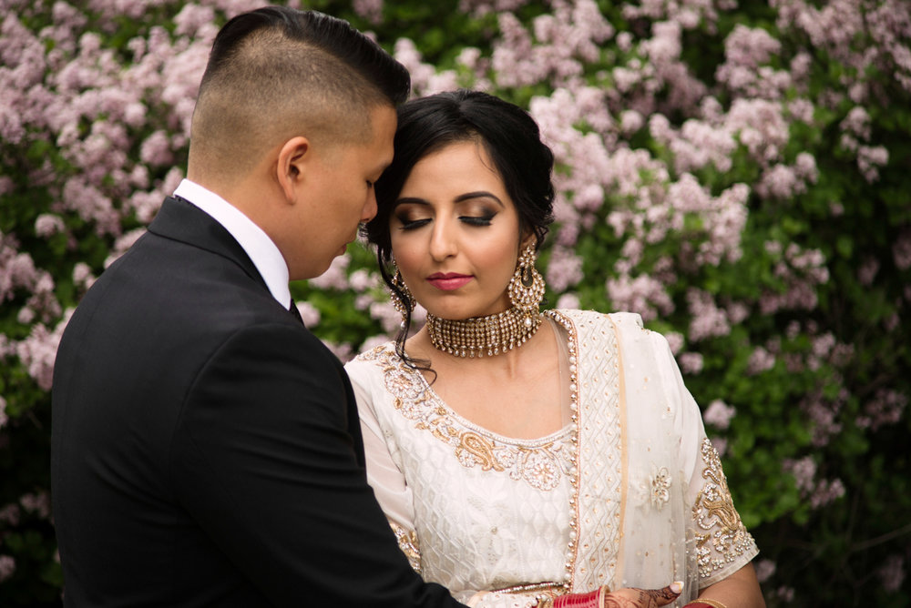 edmonton Indian and filipino wedding couple by blossoming trees