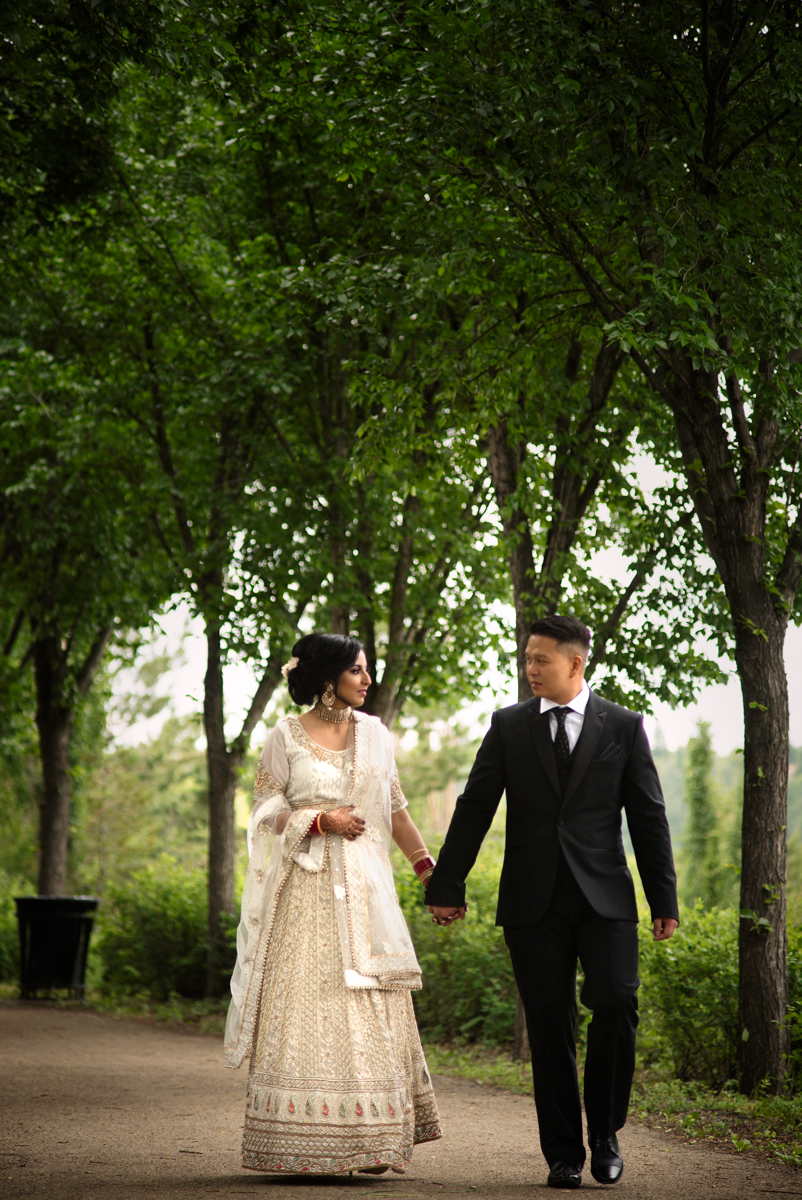 edmonton Indian and filipino wedding couple walking down park path