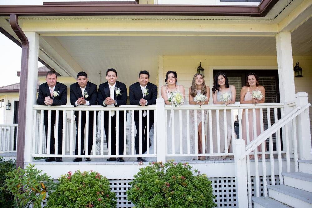 Private Estate Wedding in Boone, NC wedding party leaning against house's porch railing