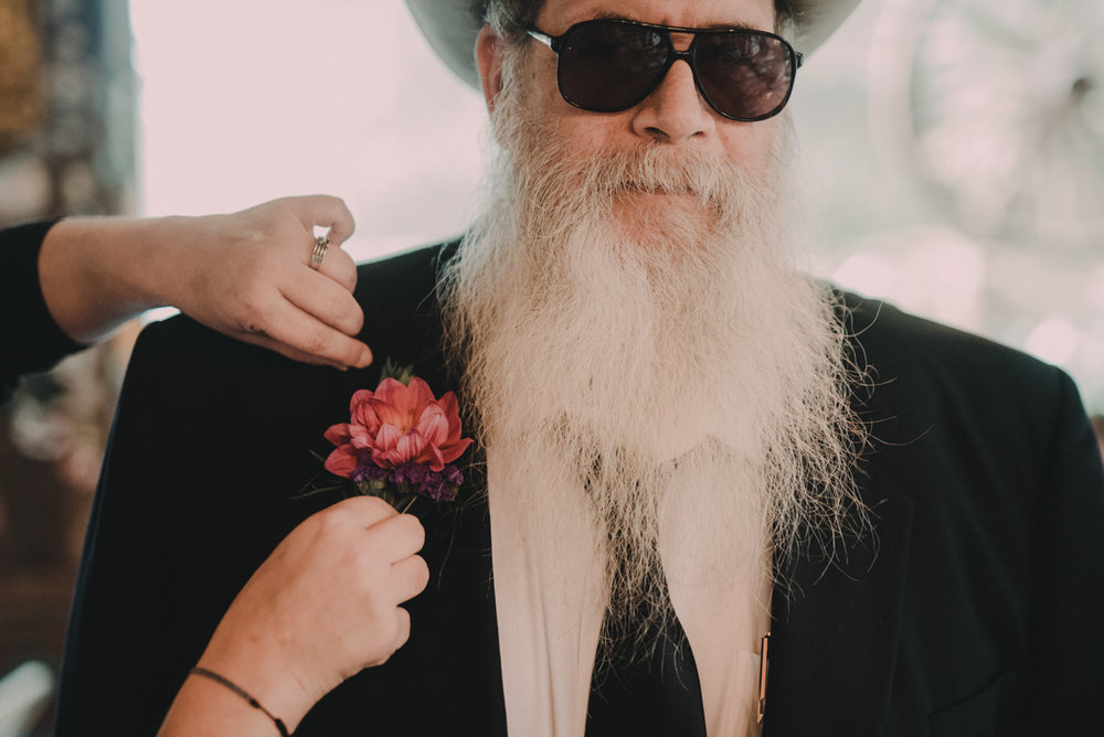 intimate, eclectic austin wedding bearded guest getting flower pinned to lapel
