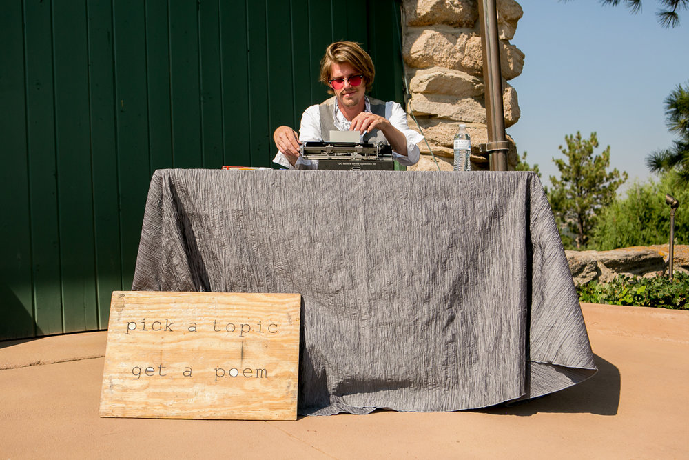 """colorado castle wedding poet at table with sign reading """"pick a topic, get a poem"""""""