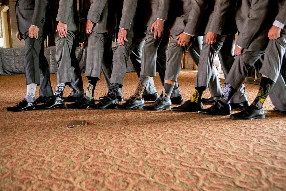 colorado castle wedding groomsmen showing off fun socks