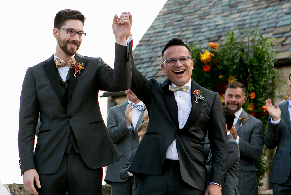 colorado castle wedding newlyweds leaving ceremony with held hands raised