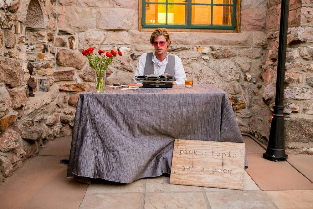colorado castle wedding poet typing at table