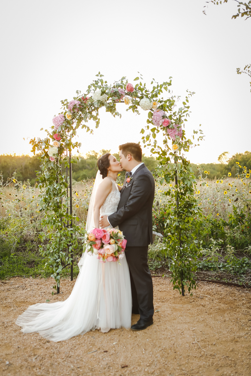 Dreamy pastels dallas texas kiss under floral arch